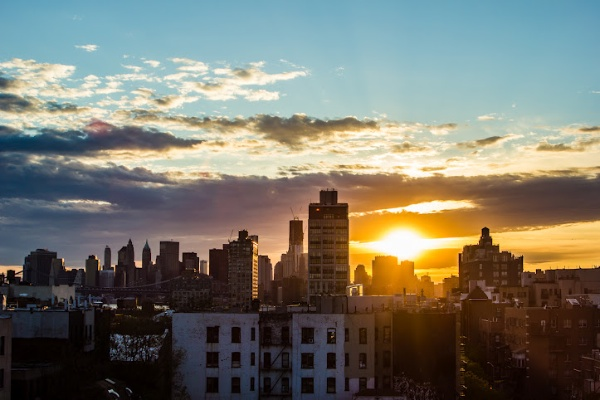 An image of a sun setting behind a cityscape
