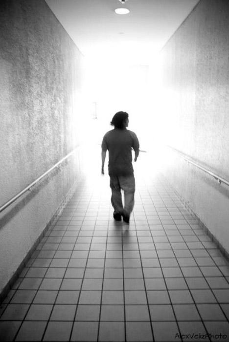 A black and white photo of a man walking down a corridor
