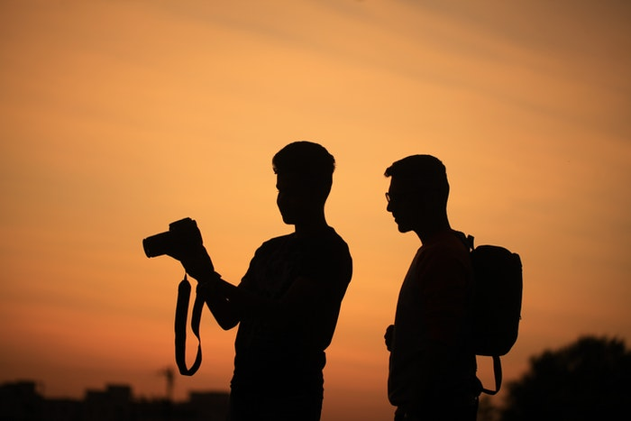 Two photographers silhouetted against the sunset