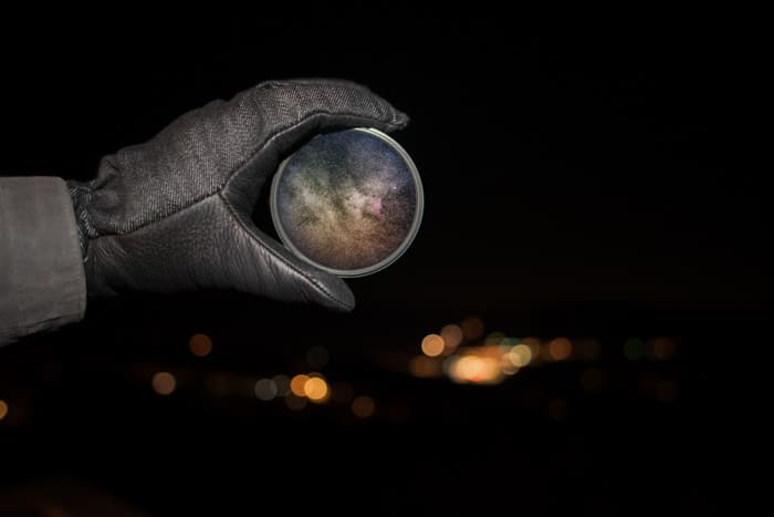 A gloved hand holding a camera filter at night