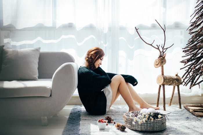 A girl sitting on a living room floor with christmas decorations a round - christmas photography tutorials