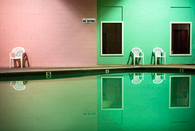 Interestingly coloured shot of a swimming pool, with the pink and green painted walls reflected in the water