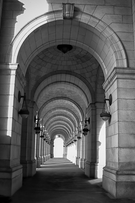 a black and white photo of repeating arches using leading lines for better photography composition