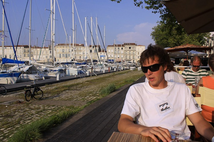 a man in sunglasses sitting in a cafe with a row of yachts to his right - leading line for better photography composition