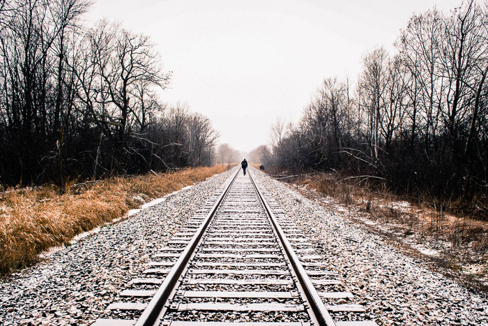 A photo of a person walking on rain tracks using leading lines composition