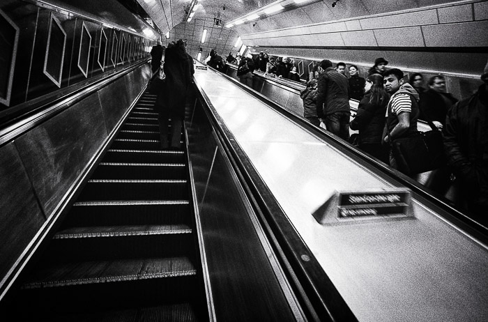 a black and white photo of going up the escalator in London's underground uding leading lines for better photo composition