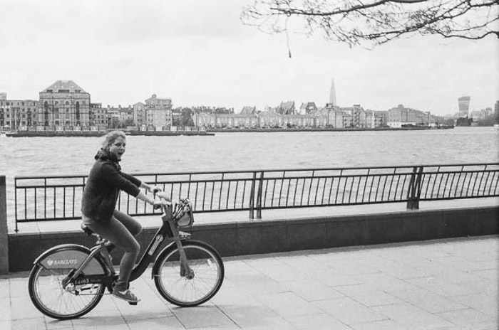 Black and white shot of a girl cycling past a river, taken with the vintage camera Rollei B35