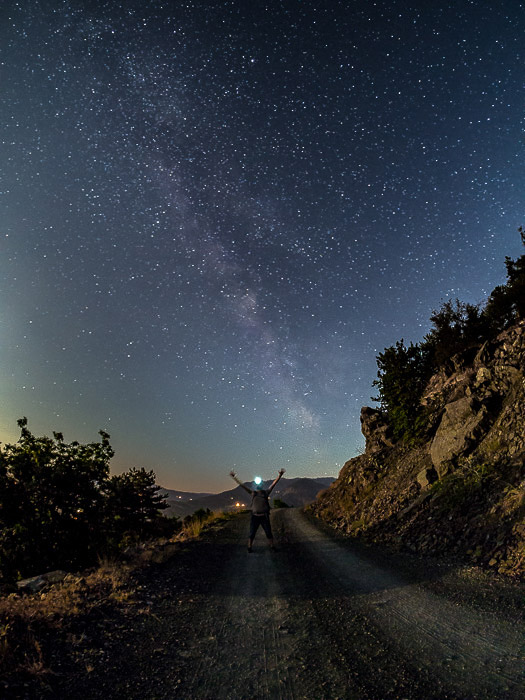 A man with outstretched arms under the Milky Way (Bobbio, Italy)