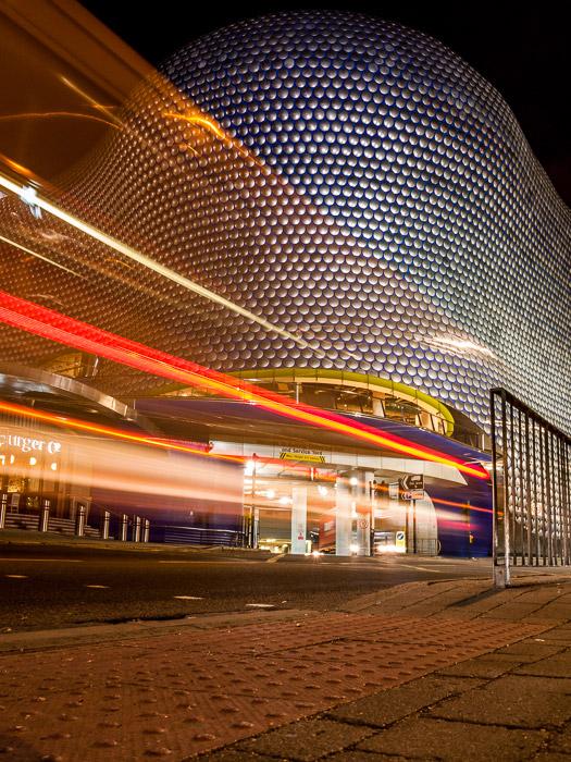 O borrão de movimento colorido de trilhas de luz em frente ao shopping center Bullring em Birmingham, Reino Unido.