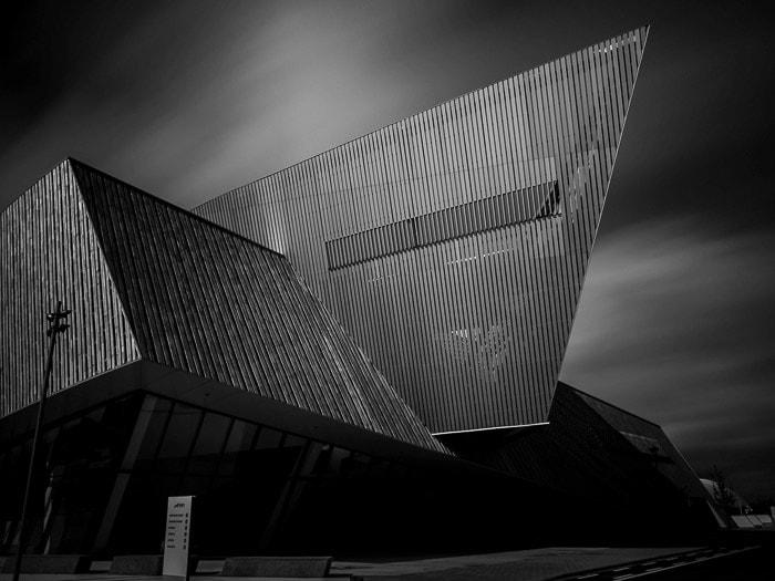 Foto em preto e branco do novo centro de congressos em Mons, Bélgica, com céu borrado de movimento