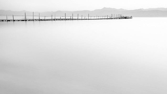 Minimal photo of a dock in Kalamaki beach at dawn. (Kerkyra, Greece), demonstrating smooth motion blur