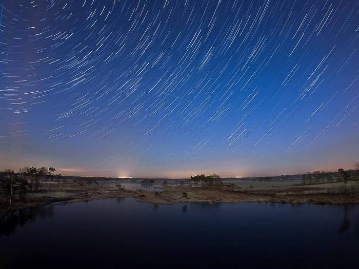 Nocurnal landscape over water, creative motion blur star trails above