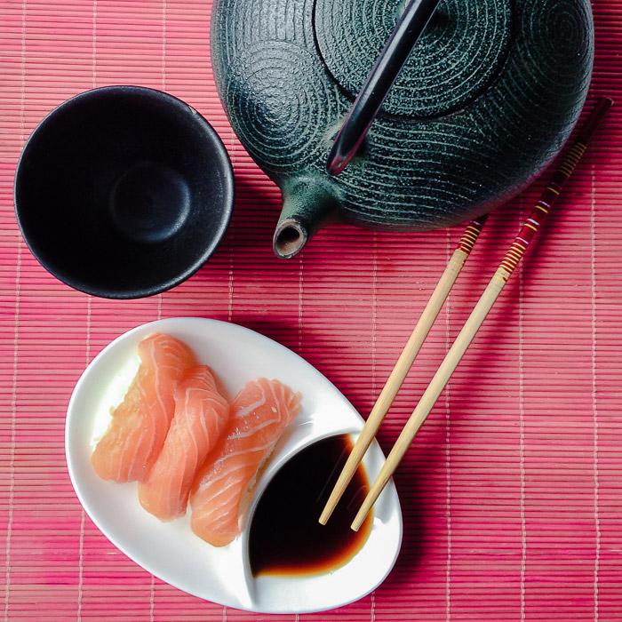 Una fotografía cenital de sushi, tetera y taza de té para fotografías de naturaleza muerta