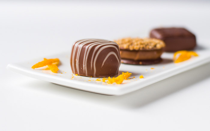 bright and airy still life photography of Belgian pralines decorated with orange peel.