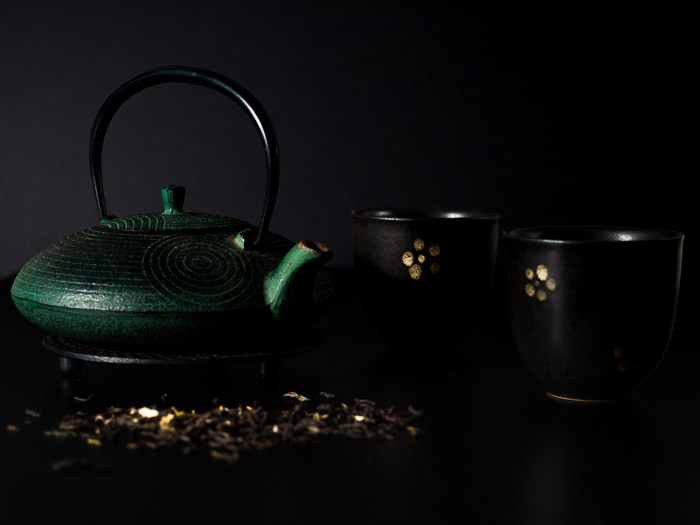 A dark, moody shot of a teapot and teacups for still life photography