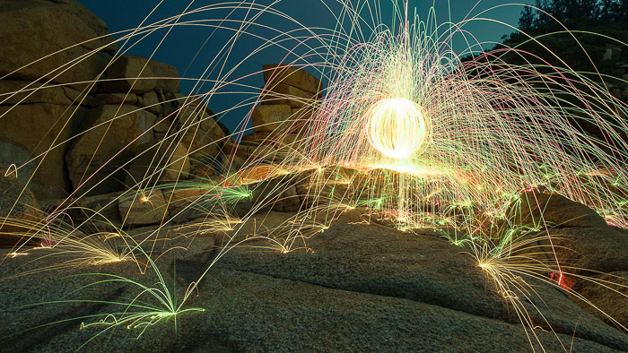 A glowing ball with colored sparks being emitted from Steel Wool Spark Photography