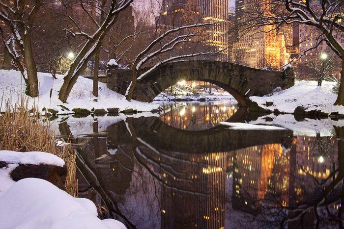A snow covered bridge over a river in the foreground of a cityscape