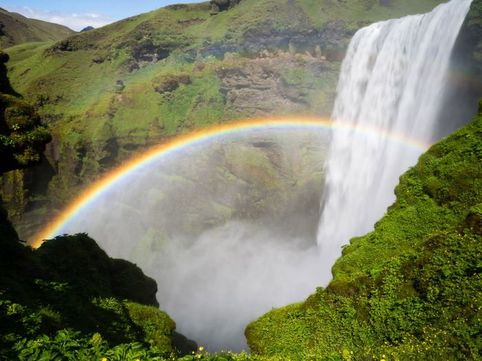 Magnificent shot of a rainbow over a waterfall