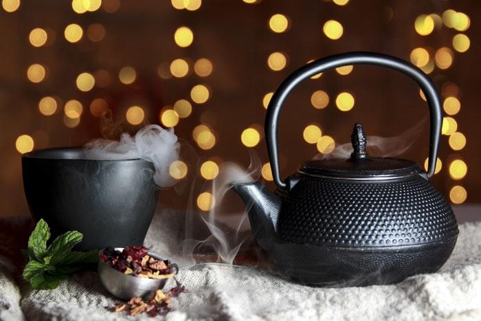 Black tea pot and mug with bokeh background