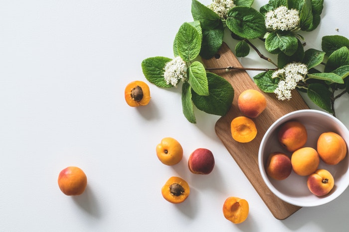 A still life photo of fruit and flowers
