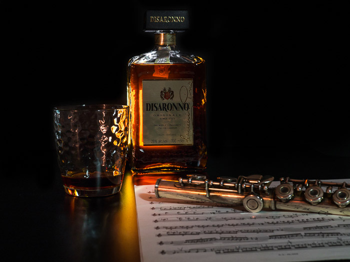 Atmospheric still life photography shoot of a clarinet and bottle of Disaronno