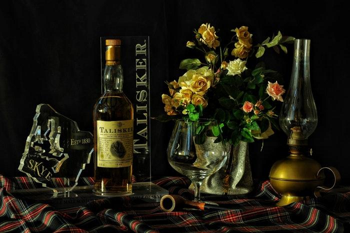 Un disparo de bodegón de una botella de whisky dispuesta con rpops y flores.