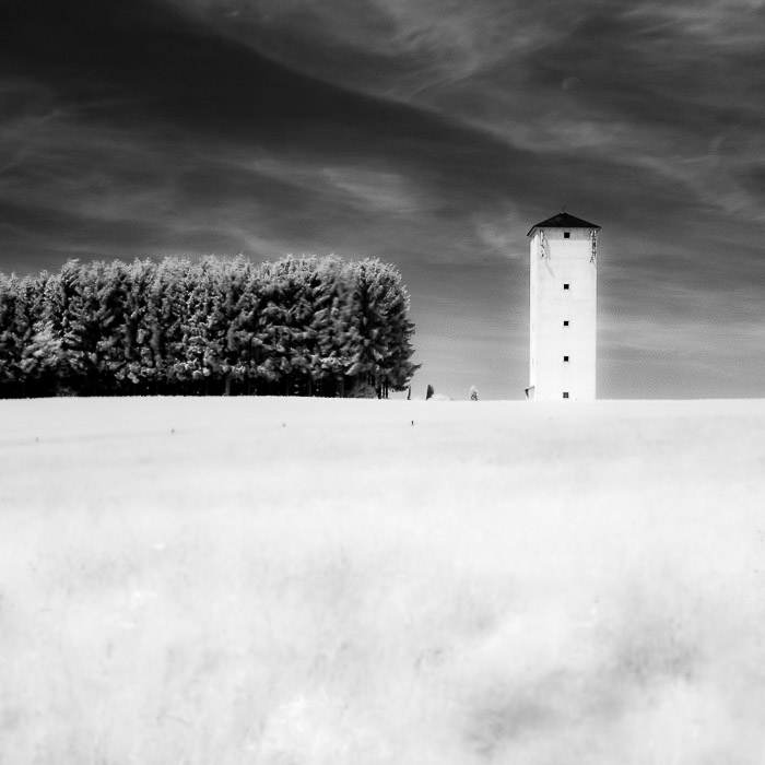 An infrared photography shot of a tower in the countryside, demonstrating symmetry in photography