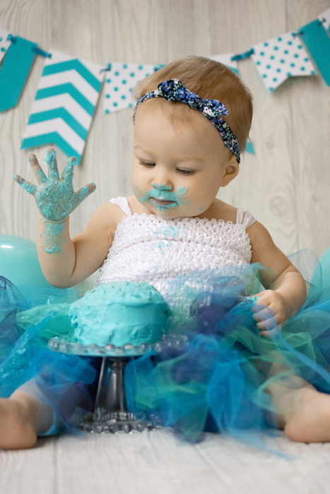 Portrait of a young baby smashing a green cake - DIY Cake Smash Photography