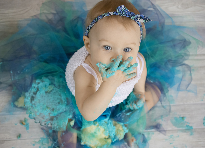 Cute portrait of a baby eating a green cake and looking up at the camera - DIY Cake Smash Photography