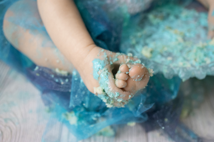 close up shot of a baby messily covered in cake