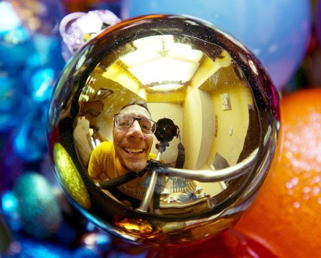 Una fotografía de un hombre visto en el reflejo de una chuchería navideña - Proyectos de fotografía para hacer con niños