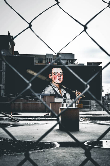 A street photo of graffiti shot through a chain link fence with a 50mm lens