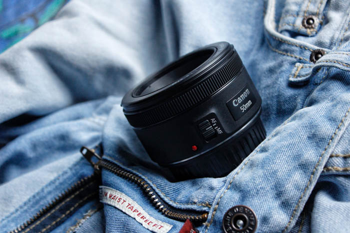 A canon 50mm lens resting on a denim jacket