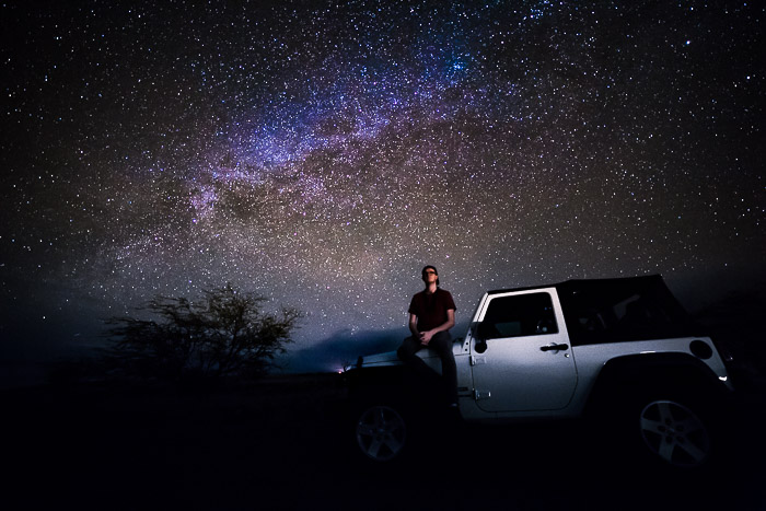 A Milky Way Photographer sitting on a car bonnet under a star filled sky