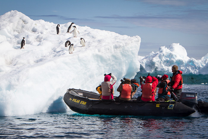 A group of people on a raft photographing penguins on an iceberg