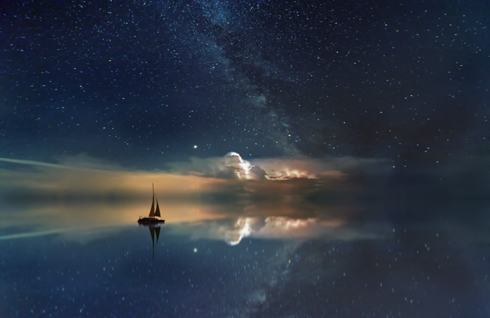An image of a boat on a reflective lake showing the milky way