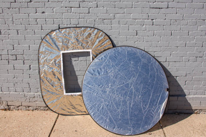 two photography reflectors by a wall
