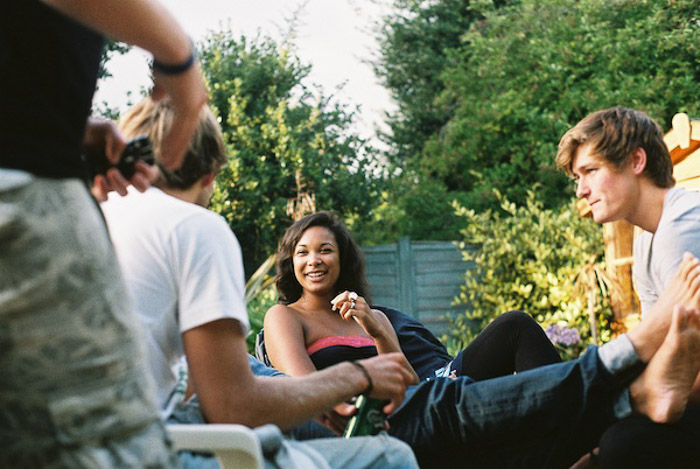 A candid portrait photo of friends chatting in a garden