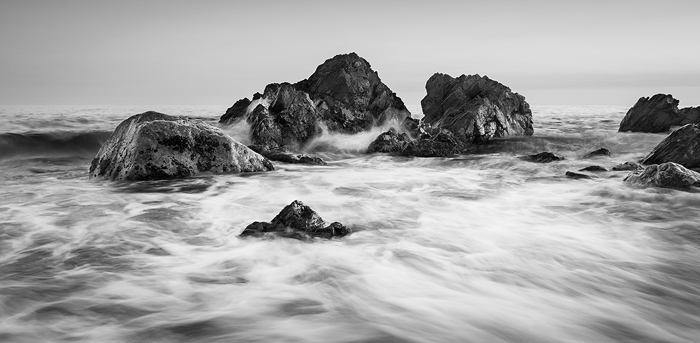 Black and white image of rocks at the seaside showing beautiful contrast