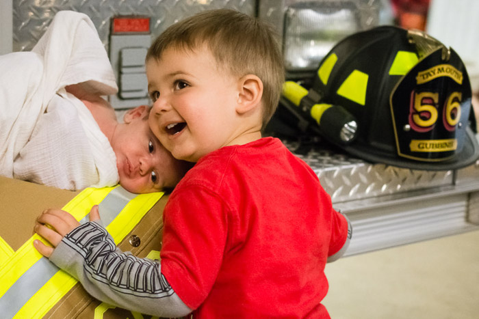 A family portrait shot of a little boy and newborn baby posed with fireman paraphernalia