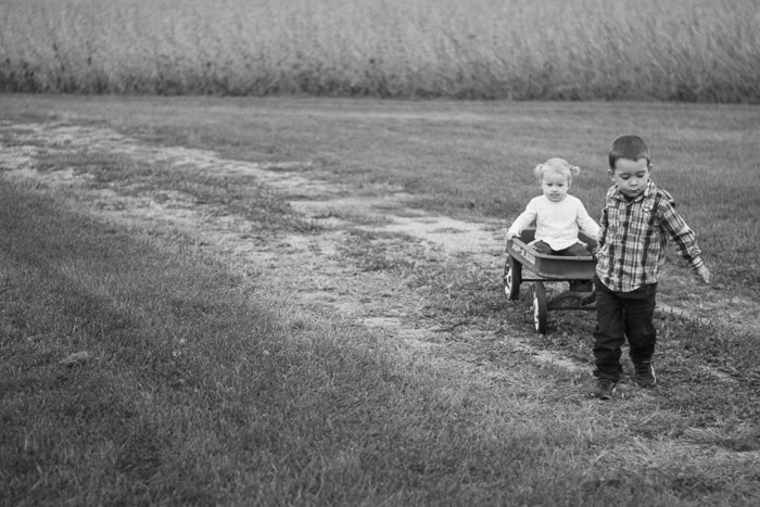 sweet and nostalgic feeling candid photo of a little boy and girl playing in fields