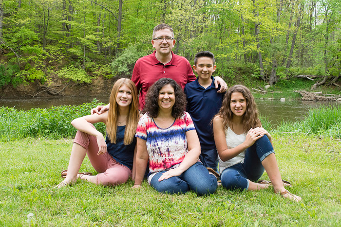 A family of 5 posing outdoors