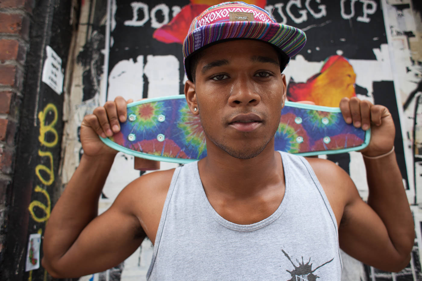 Street photography: Portrait of young man holding skateboard behind his head