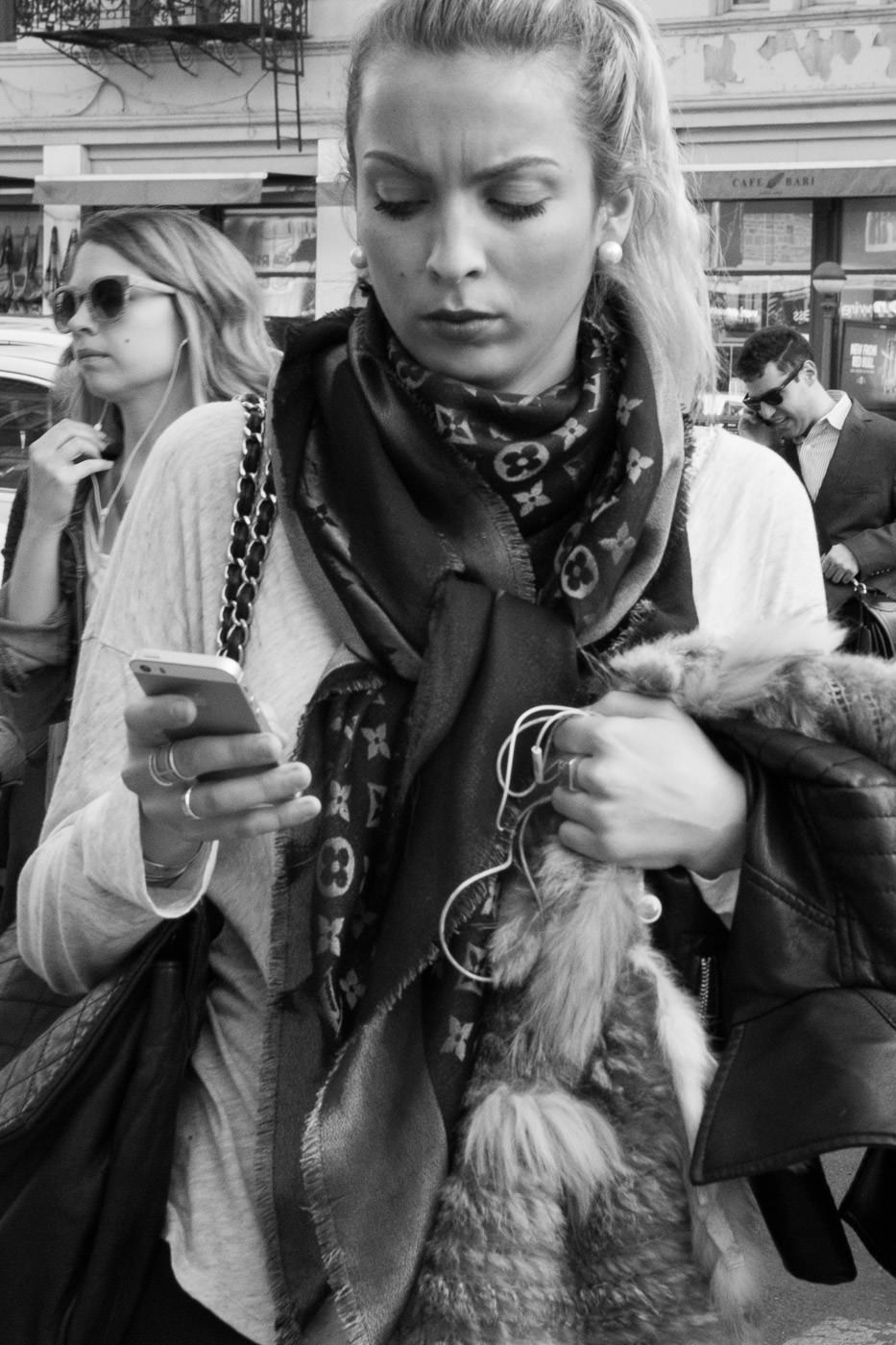 Street photography: Black and white portrait of ponytailed woman checking her phone