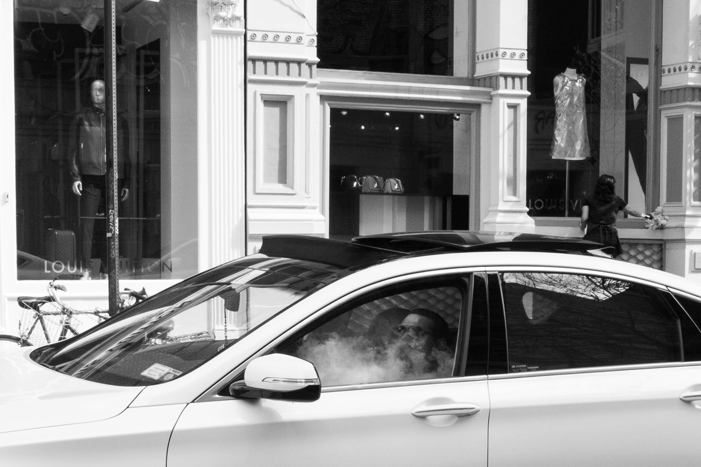 Street photography: Man smoking inside car on the street