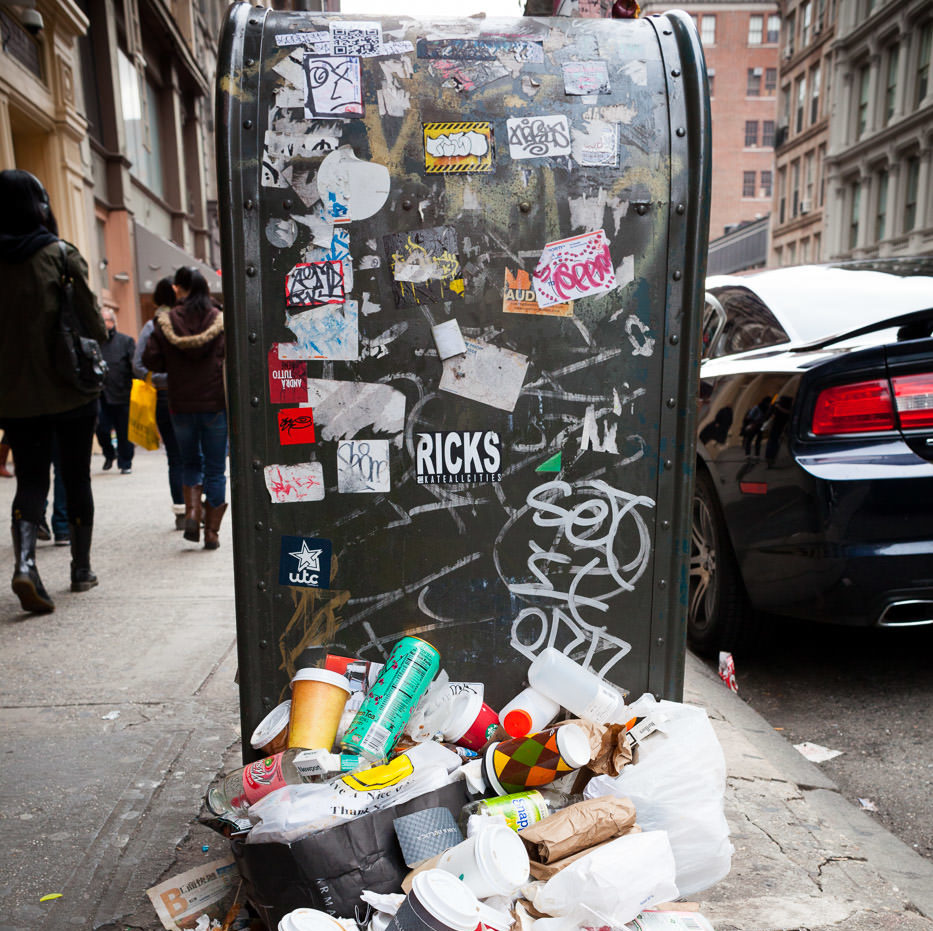 Street photography: Mailbox covered in graffiti and stickers with pile of trash in foreground