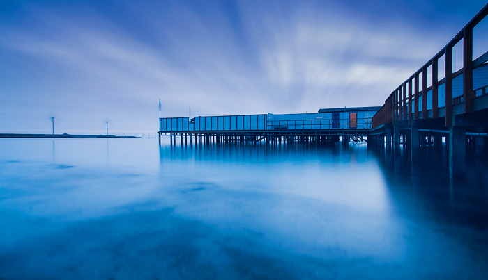 Natural blue monochrome long-exposure photo of boathouse on water