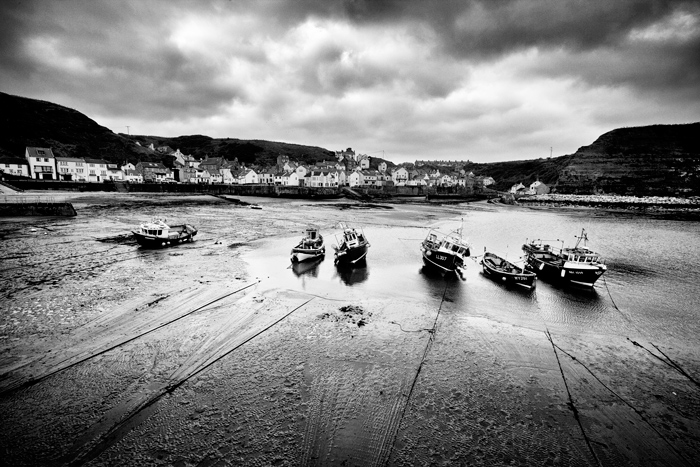 A Black and white landscape photo of a line of boats sitting in harbour at low tide