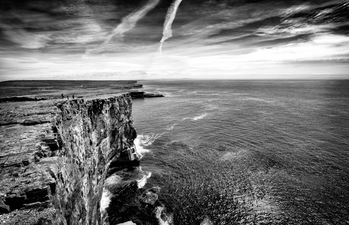 A black and white shot of a cliff overlooking water
