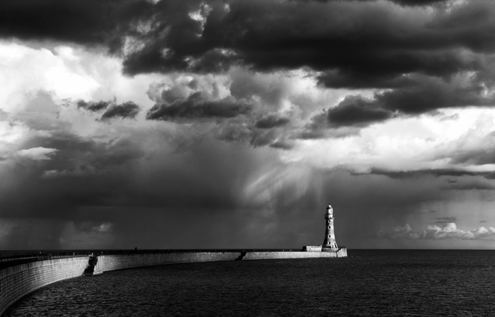 A stunning black and white shot of sun-kissed lighthouse on promontory with dark clouds overhead